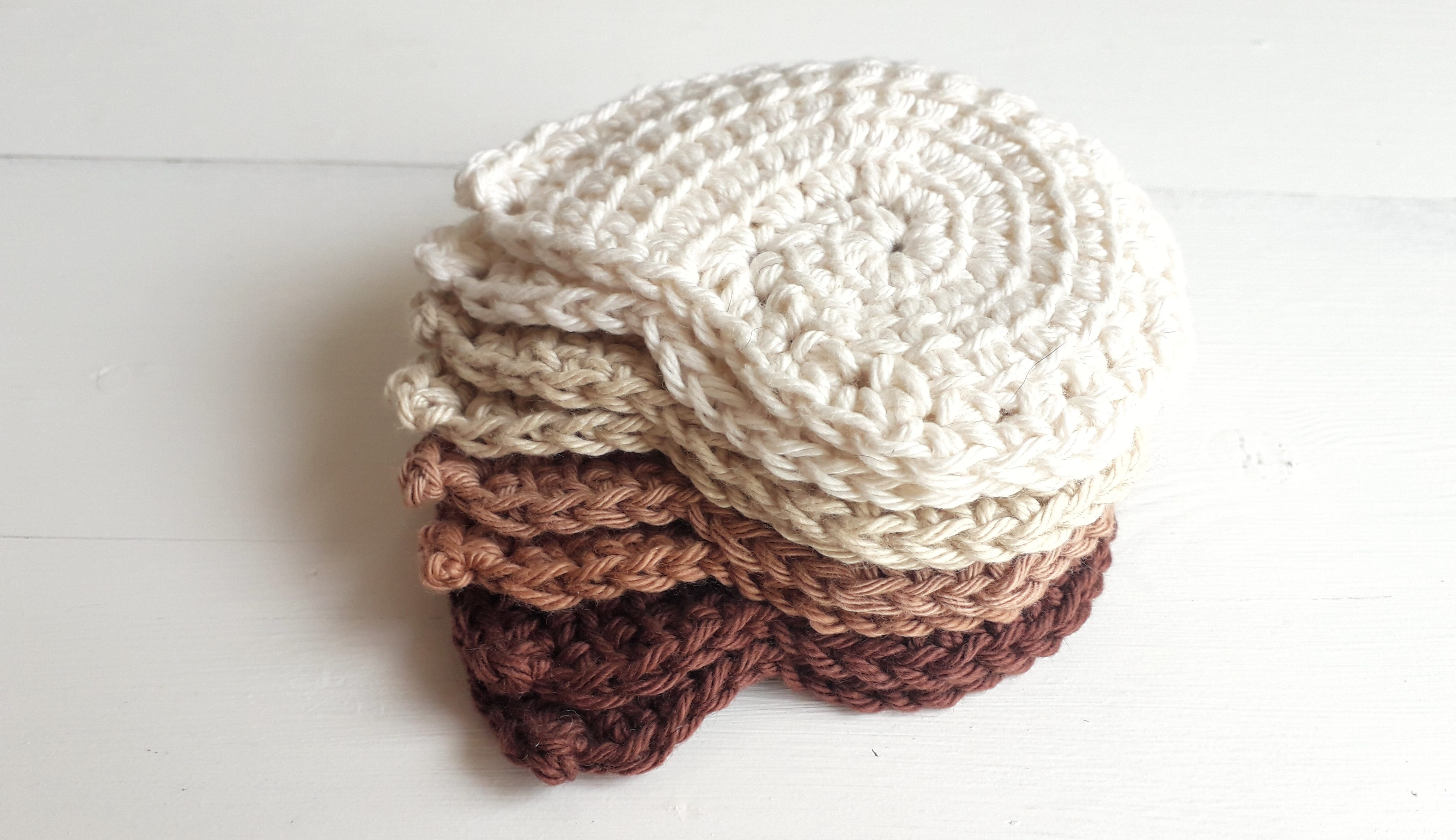 a pile of spiral crochet face scrubbies, piled from dark (at the bottom) to light (at the top)
